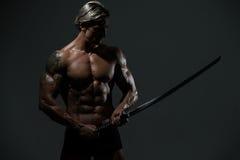 有长的剑的战士在黑背景 库存照片