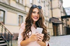 有长的卷发和电话的在手上微笑对照相机的逗人喜爱的女孩Portraut在大厦背景的城市 免版税库存照片