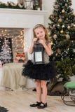 有长的卷发的俏丽的女孩在与一盏大枝形吊灯的一棵圣诞树 免版税库存照片
