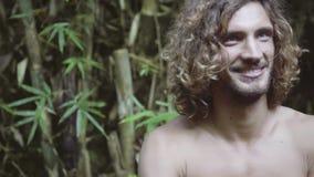 有长的卷发的可爱的年轻人离开背包赤裸后面 股票录像