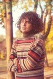 有长的卷发的可爱的年轻人,穿戴在镶边毛线衣在秋天公园 库存照片
