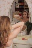 有长的卷发的性感的年轻美丽的妇女在肉欲的淡色女用贴身内衣裤在镜子附近在家投入了perls 库存照片