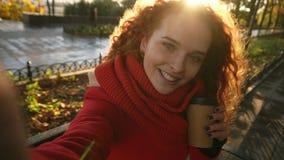 有长的卷发的愉快的白种人妇女在一件温暖的外套和围巾步行通过秋天公园有黄色叶子的 影视素材
