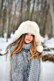 有长的卷发的美丽的女孩在被编织的围巾和裘皮帽获得乐趣室外在冬天森林在雪花下 图库摄影