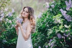 有长的卷发的美丽的少妇在有丁香的一个庭院里 图库摄影