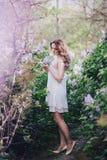 有长的卷发的美丽的少妇在有丁香的一个庭院里 免版税库存照片