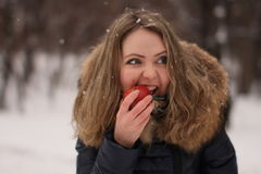 有长的卷发的美丽的愉快的女孩用一个苹果在她的手上 免版税图库摄影