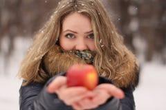 有长的卷发的美丽的愉快的女孩用一个苹果在她的手上 免版税库存照片