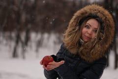 有长的卷发的美丽的愉快的女孩用一个苹果在她的手上 库存照片