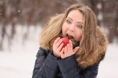 有长的卷发的美丽的愉快的女孩用一个苹果在她的手上 免版税库存图片