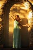有长的卷发的美丽的金发碧眼的女人在户外静止的一件长的晚礼服在夏天日落的减速火箭的葡萄酒大厦附近 库存图片
