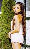 有长的卷发的年轻俏丽的妇女外面在穿时髦的性感的白色礼服,生活方式人概念的绿色公园 免版税库存照片