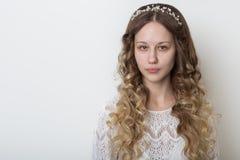 有长的卷发的年轻美丽的女孩,与一张干净的面孔的没有构成与在他的顶头画象的一个花圈在a的演播室 免版税库存照片