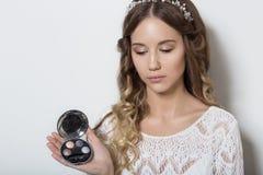 有长的卷发的年轻美丽的女孩,与一张干净的面孔的没有构成与在他的顶头画象的一个花圈在a的演播室 免版税库存图片