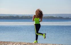 有长的卷发的年轻,美丽,运动妇女早晨在海滩,由湖负责 免版税库存照片