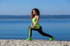 有长的卷发的年轻,美丽,运动妇女早晨在海滩,由湖负责 图库摄影
