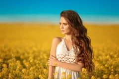 有长的卷曲健康头发的美丽的无忧无虑的女孩在黄色强奸领域风景背景 有吹的Attracive浅黑肤色的男人 免版税库存照片
