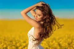 有长的卷曲健康头发的美丽的无忧无虑的女孩在黄色强奸领域风景背景 有吹的Attracive浅黑肤色的男人 图库摄影