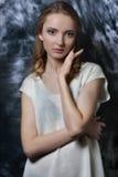 有长的卷毛头发的性感的美丽的妇女在白色女衬衫 免版税图库摄影
