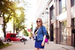 有长的发型和红色嘴唇的凉快的女孩获得乐趣在城市 她面带太阳镜和微笑对照相机 免版税图库摄影