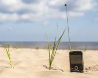 有长的天线的电话收到在一个沙滩的一个信号 免版税库存图片