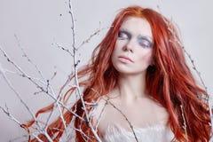 有长的头发、用雪盖的面孔与霜白色眼眉和睫毛的红头发人女孩在霜,报道的树枝 免版税库存照片