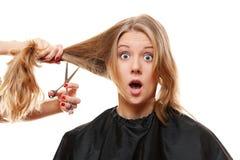 有长的头发和剪刀的惊奇妇女 免版税库存图片