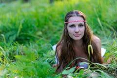 有长的头发和斯拉夫的种族服装的年轻美丽的斯拉夫的女孩在草在夏天森林里 免版税图库摄影