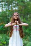 有长的头发和斯拉夫的种族礼服的一个年轻美丽的斯拉夫的女孩在有一把礼节匕首的一个夏天森林里站立在她的手上 免版税库存照片
