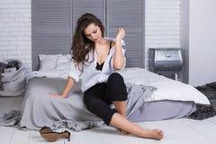 有长的头发的一个女孩在黑牛仔裤和一件白色衬衣穿戴了坐床 时兴的偶然成套装备 免版税库存图片