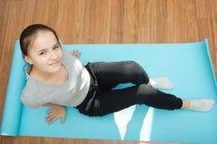 有长的头发的一个年轻欧洲女孩坐瑜伽席子 免版税库存图片