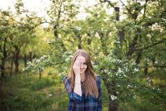 有长的头发的一个年轻美丽的女孩在一只笼子的一件蓝色衬衣到开花的苹果树里 女孩闭上了与她的h的一只眼睛 免版税库存照片
