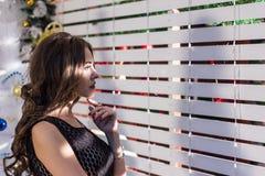 有长的头发的一个美丽的女孩在一件黑礼服周道地看一个白色木格子,明亮的光穿过 图库摄影