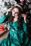 有长的头发的一个美丽的女孩在圣诞树附近的一件绿色礼服调整在她的头的白色diade 免版税图库摄影