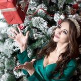 有长的头发的一个美丽的女孩在有一个保险开关的一件绿色礼服在她的胸口在装饰的圣诞树附近捉住一个红色箱子 C 库存照片