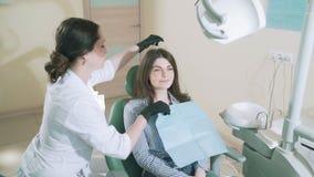 有长的头发的一个美丽的微笑的浅黑肤色的男人在时髦的衣裳在牙医` s办公室来对待她的牙 迟缓地 影视素材