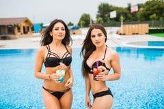 有长的头发的两个可爱的女孩在太阳的水池附近摆在并且喝鸡尾酒 他们穿有太阳镜的泳装 他们 免版税库存照片