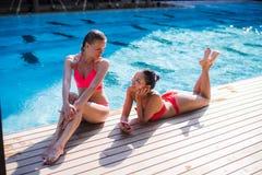 有长的头发的两个可爱的白肤金发和深色的女孩在弗洛尔说谎在水池附近 他们穿比基尼泳装和泳装 他们 免版税库存图片