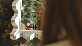 有长的头发的两个年轻性感的金发碧眼的女人为党做准备,坚持镜子和微笑 影视素材