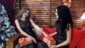有长的头发的两个美丽的女孩在黑礼服是谈话和微笑与假日箱子在他们的圣诞节的手上或新的 库存照片
