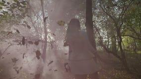有长的头发的十几岁的女孩享受一photoshoot的在森林里在与抽烟的一秋天天在慢动作- 影视素材