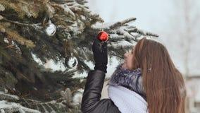 有长的头发的可爱的女孩在摆在反对一棵多雪的树的冬天衣服 女孩串起圣诞节球 影视素材