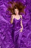有长的头发的女孩在紫色织品 免版税库存图片