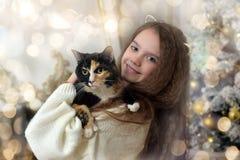 有长的头发的女孩有在她的胳膊的一只猫的 免版税库存图片
