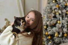 有长的头发的女孩有在她的胳膊的一只猫的 库存照片