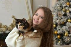 有长的头发的女孩有在她的胳膊的一只猫的 免版税库存照片
