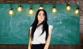 有长的头发的妇女在白色女衬衫在教室站立 准备好的老师开始教训,拷贝空间 精华学校 库存照片