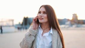 有长的头发的少妇沿街道在电话走并且谈话 股票视频