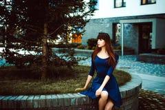 有长的头发的年轻可爱的妇女在与配刀腰带的一身蓝色庄重装束 免版税图库摄影