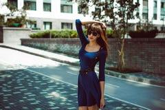 有长的头发的年轻可爱的妇女在与配刀腰带的一身蓝色庄重装束 免版税库存照片